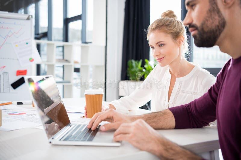 Hombre de negocios y empresaria que trabajan con el ordenador portátil junto en lugar de trabajo en oficina fotografía de archivo libre de regalías
