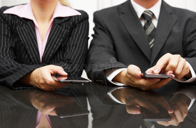 Hombre de negocios y empresaria que usa el teléfono elegante en la reunión fotografía de archivo libre de regalías