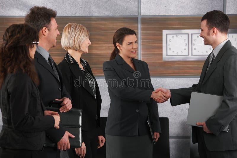 Hombre de negocios y empresaria que sacuden las manos fotografía de archivo