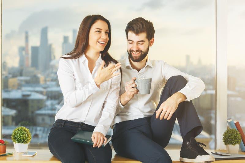 Hombre de negocios y mujer jovenes en alféizar imágenes de archivo libres de regalías