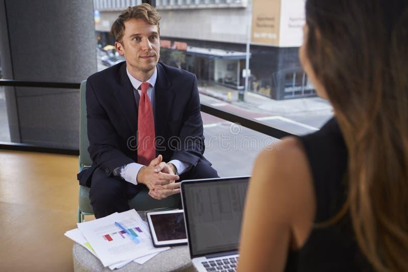 Hombre de negocios y mujer jovenes en una reunión informal en oficina foto de archivo