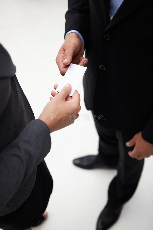Hombre de negocios y mujer que intercambian una tarjeta de visita imagenes de archivo