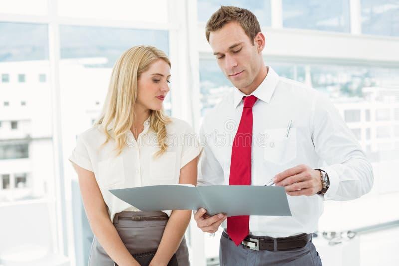 Hombre de negocios y secretaria que miran el fichero en oficina imagenes de archivo