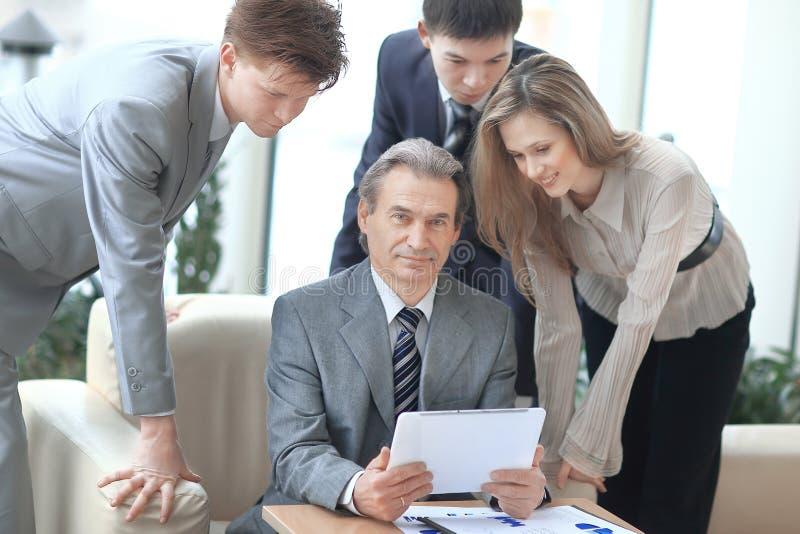 Hombre de negocios y sus colegas que se sientan en la tabla en la oficina imagen de archivo