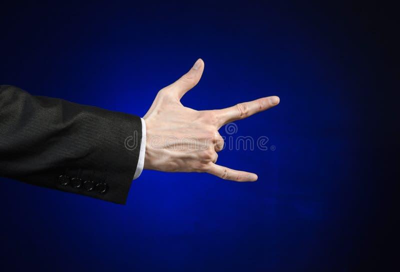 Hombre de negocios y tema del gesto: un hombre en un traje negro y una camisa blanca que muestran gesto de mano en un fondo azul  imágenes de archivo libres de regalías