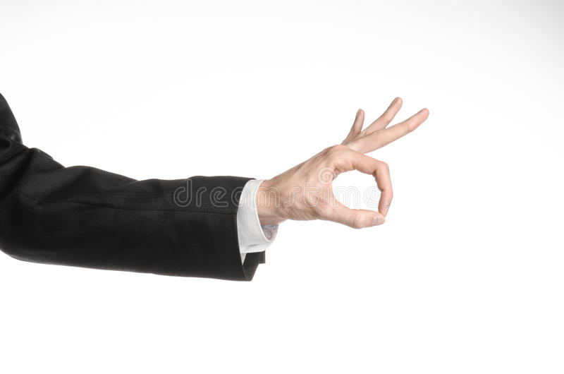 Hombre de negocios y tema del gesto: un hombre en un traje negro y una camisa blanca que muestran gesto de mano en un fondo blanc fotografía de archivo