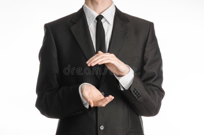 Hombre de negocios y tema del gesto: un hombre en un traje y un lazo negros que llevan a cabo las manos en el frente aislado en e fotografía de archivo
