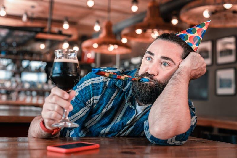 Hombre de ojos azules que sostiene el vidrio de cerveza oscura mientras que asiste a cumpleaños foto de archivo