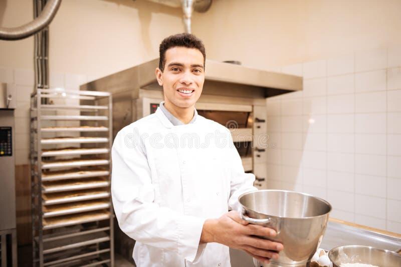 Hombre de ojos oscuros joven que siente el funcionamiento feliz en panadería agradable foto de archivo