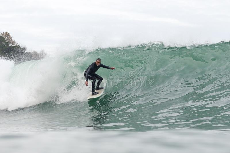 Hombre de 68 a?os que practica surf una onda grande fotografía de archivo