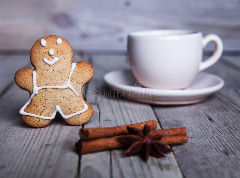 Hombre de pan de jengibre hecho en casa de la Navidad en fondo de madera Taza de café grande imágenes de archivo libres de regalías