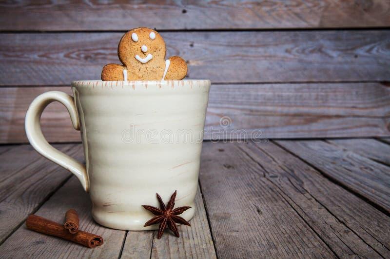 Hombre de pan de jengibre hecho en casa de la Navidad en fondo de madera Taza de café grande Anís del canela y de estrella imágenes de archivo libres de regalías