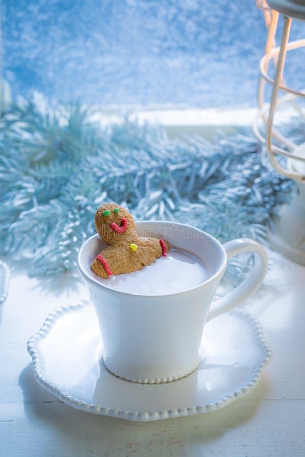 Hombre de pan de jengibre hecho en casa en el chocolate caliente para la Navidad imagen de archivo libre de regalías