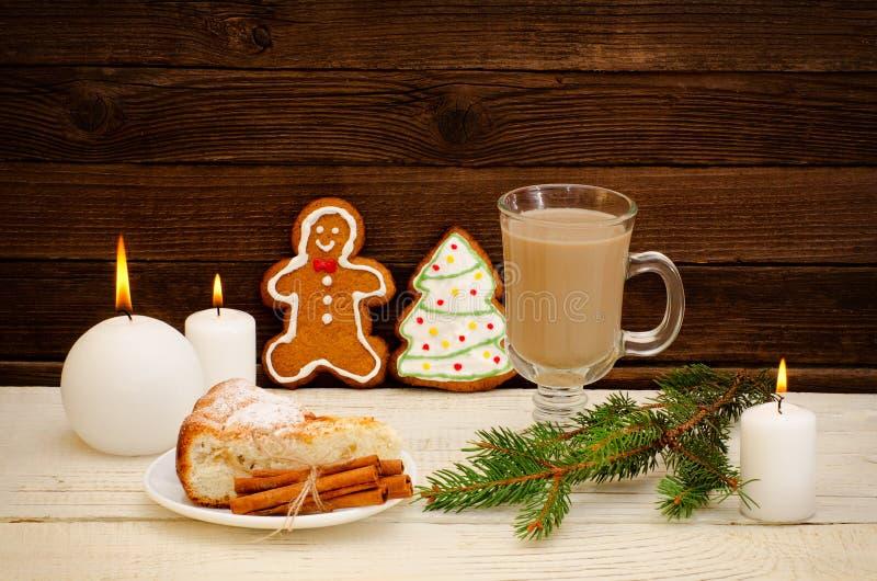 Hombre de pan de jengibre y árbol de navidad, capuchino, ramita del abeto, tarta de manzanas y velas en el fondo de madera foto de archivo