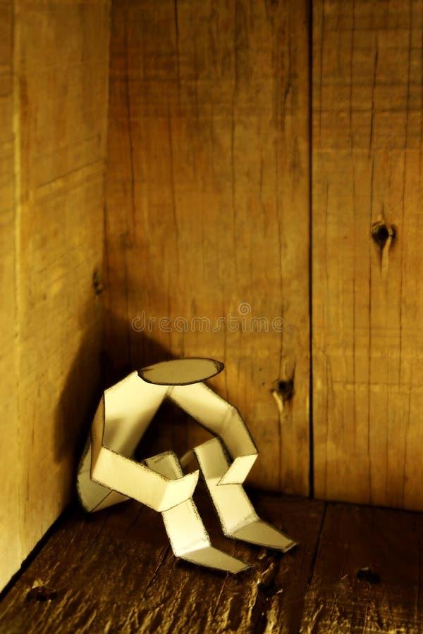 Hombre de papel en una esquina oscura imagen de archivo libre de regalías