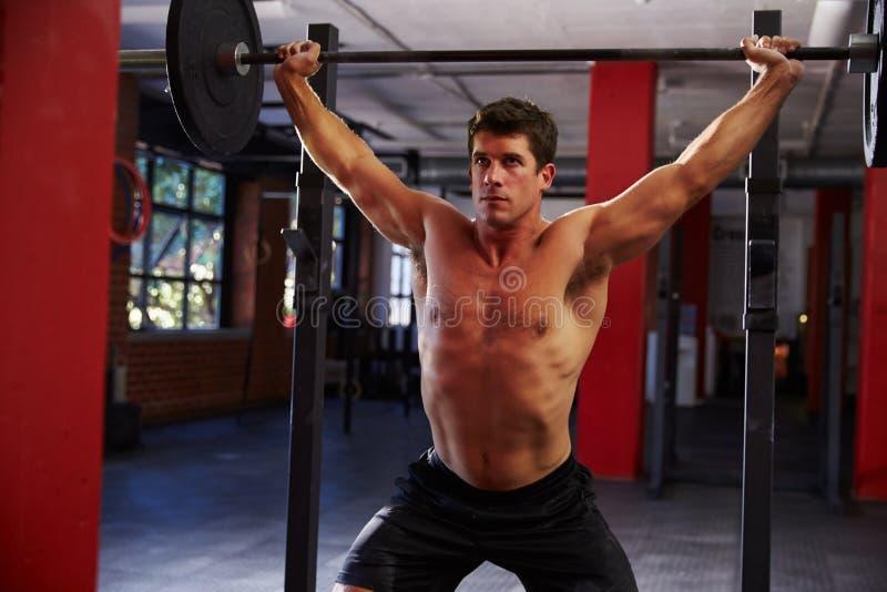 Hombre de pecho desnudo en pesos de elevación del gimnasio foto de archivo