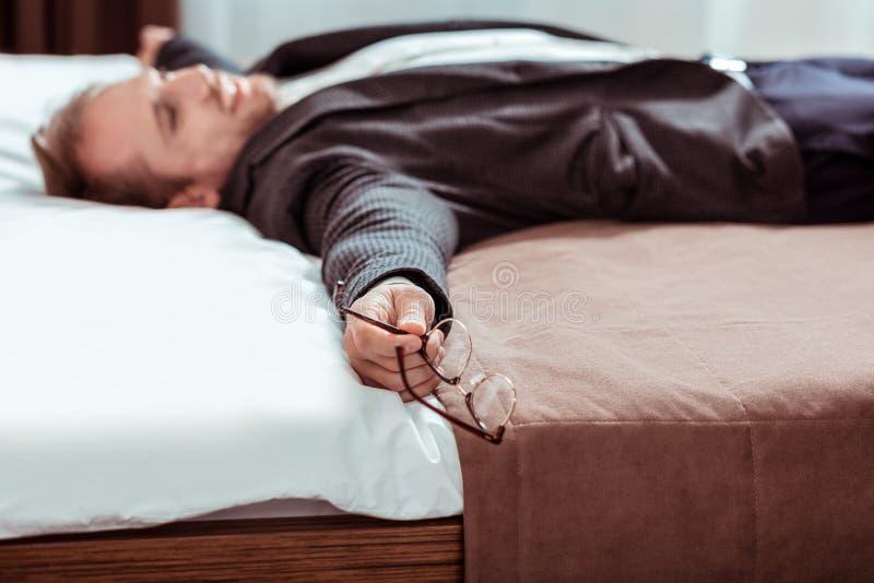 Hombre de pelo corto cansado que miente en la cama en un traje foto de archivo libre de regalías