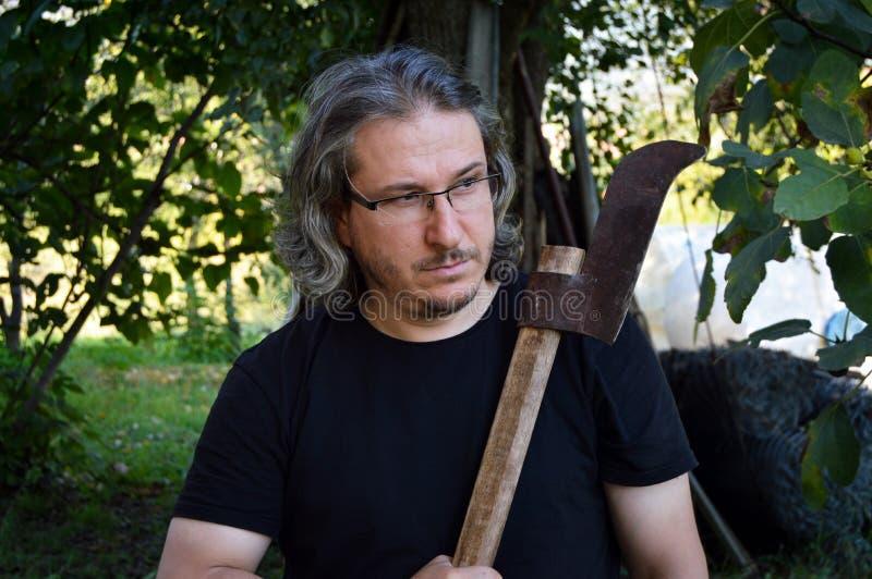Hombre de pelo largo con el hacha imagen de archivo libre de regalías