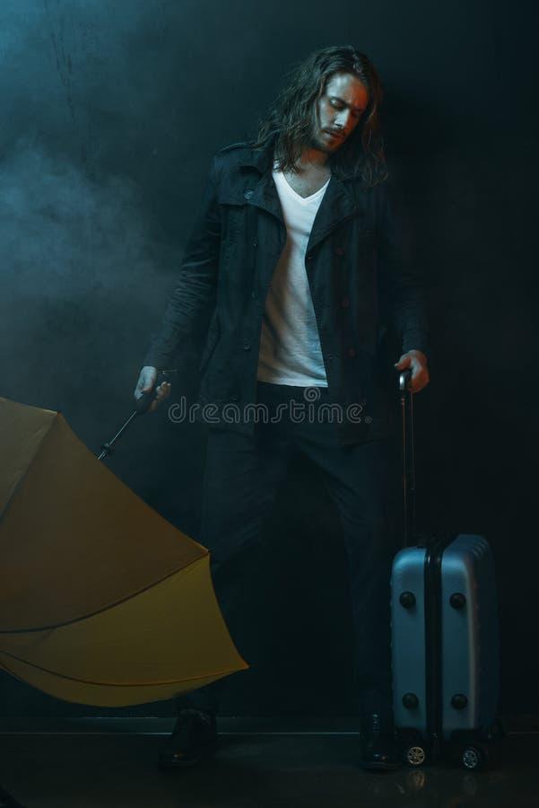 Hombre de pelo largo joven que sostiene el paraguas y la maleta amarillos imagenes de archivo