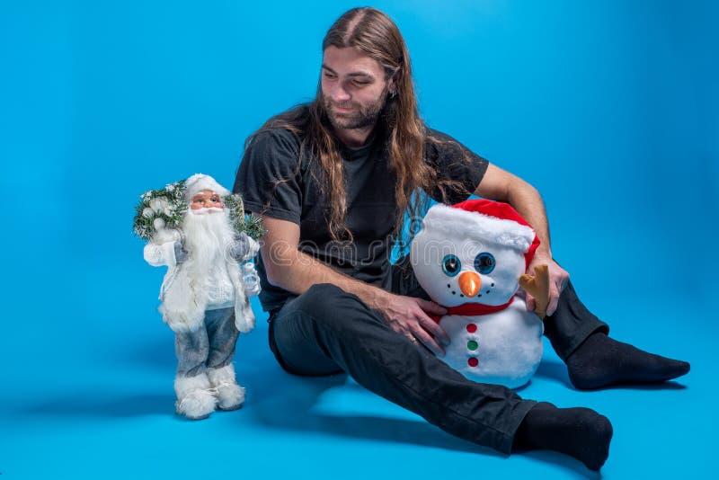 Hombre de pelo largo que mira el juguete de Santa Claus mientras que sostiene un muñeco de nieve y siéntase fotos de archivo libres de regalías