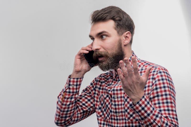 Hombre de pelo oscuro barbudo que siente enojado mientras que teniendo conversación telefónica foto de archivo libre de regalías