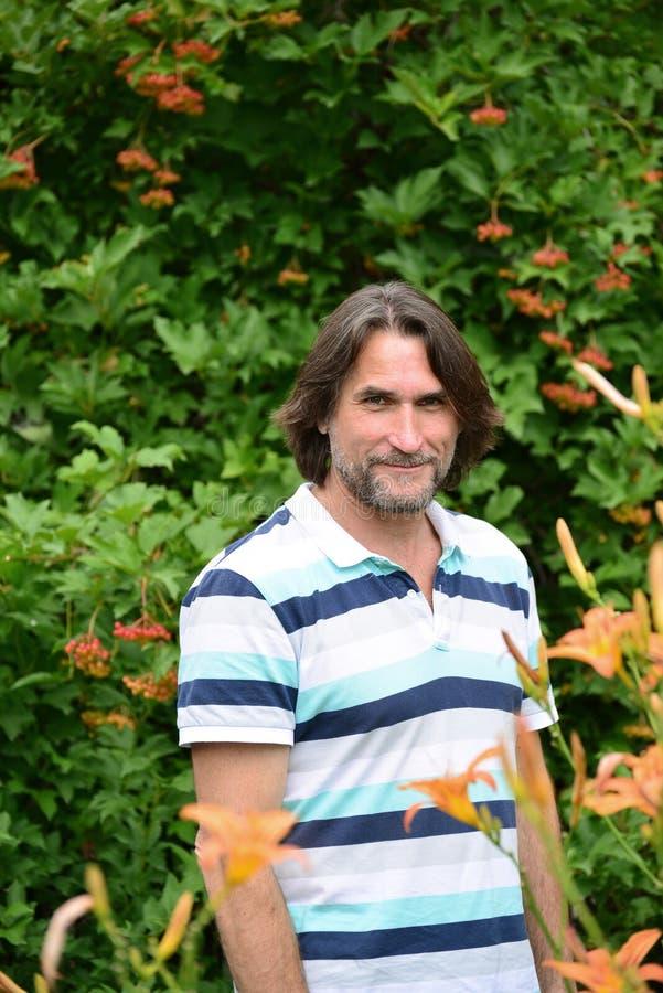 hombre de pelo oscuro con una barba en naturaleza imagen de archivo libre de regalías