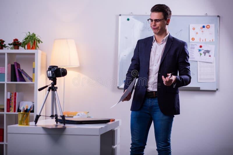 Hombre de pelo oscuro confuso en chaqueta negra que habla en cámara imagen de archivo