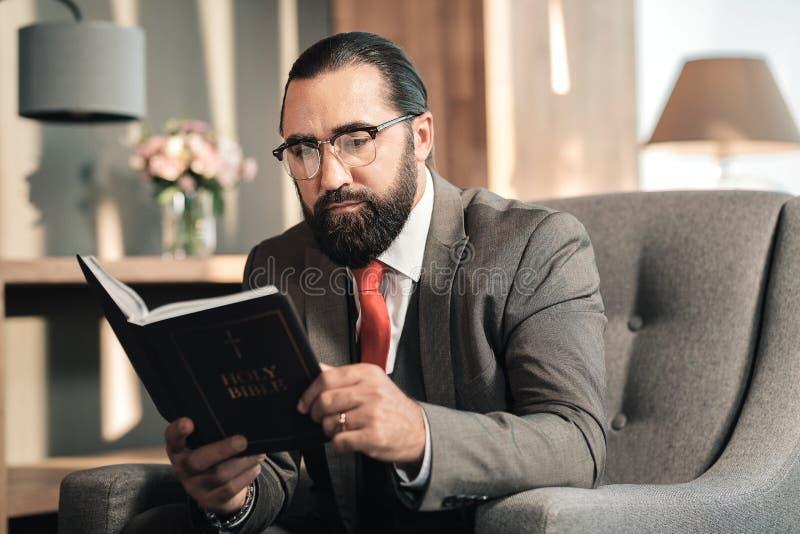 Hombre de pelo oscuro que disfruta de su tiempo mientras que lee la biblia imágenes de archivo libres de regalías