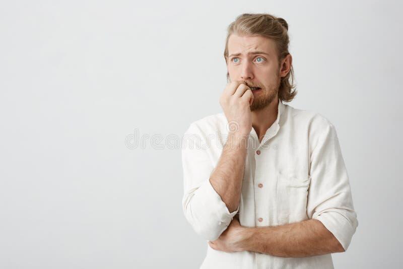 Hombre de pelo rubio atractivo con los ojos azules y los clavos penetrantes de la barba, frunciendo el ceño y mirando a un lado,  imagen de archivo libre de regalías