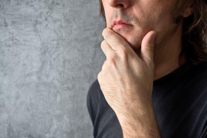 Hombre de pensamiento con la mano en su barbilla fotos de archivo libres de regalías