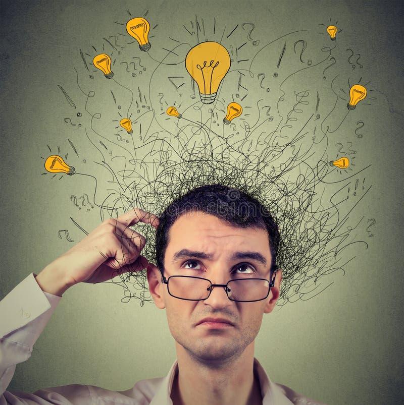 Hombre de pensamiento con las muestras de la pregunta y los bulbos ligeros de la idea sobre la cabeza que mira para arriba fotos de archivo libres de regalías