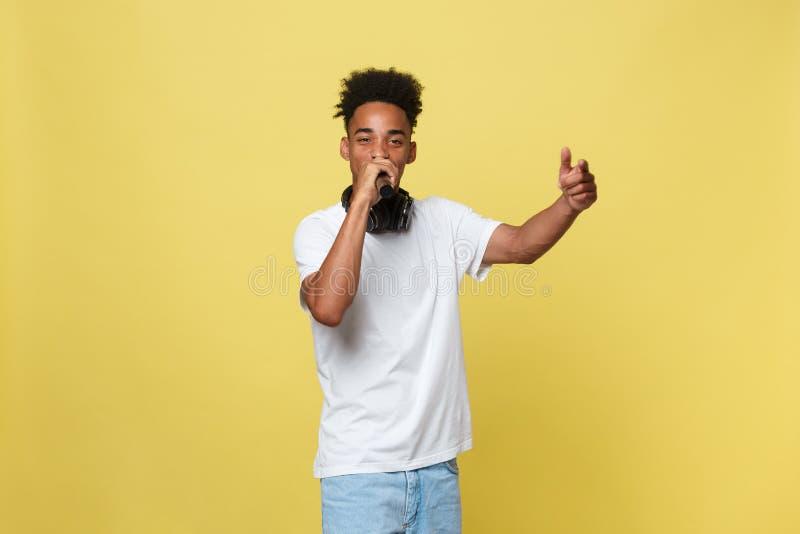 Hombre de piel morena joven atractivo con corte de pelo afro en la camiseta blanca, gesticulando con las manos y el micrófono, ba imagen de archivo libre de regalías