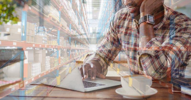 Hombre de raza mixta con compras en línea por laptop en un almacén lleno de cajas fotografía de archivo