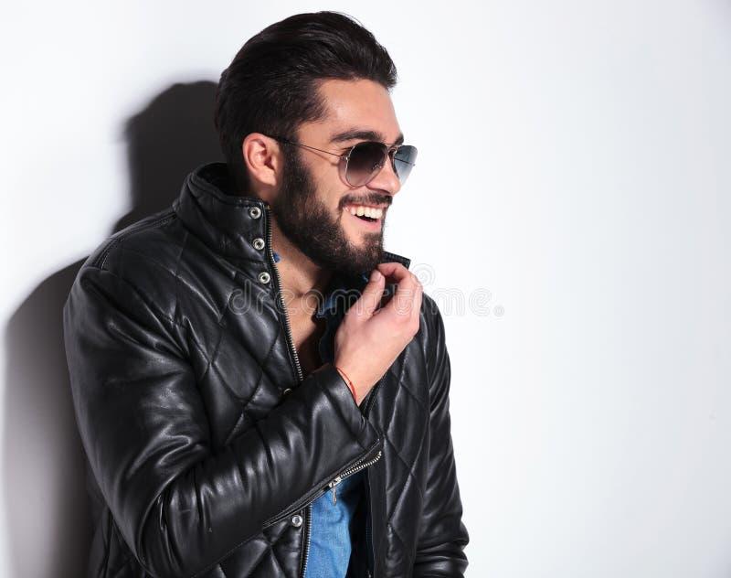 Hombre de risa en la chaqueta de cuero que tira de su barba fotos de archivo libres de regalías