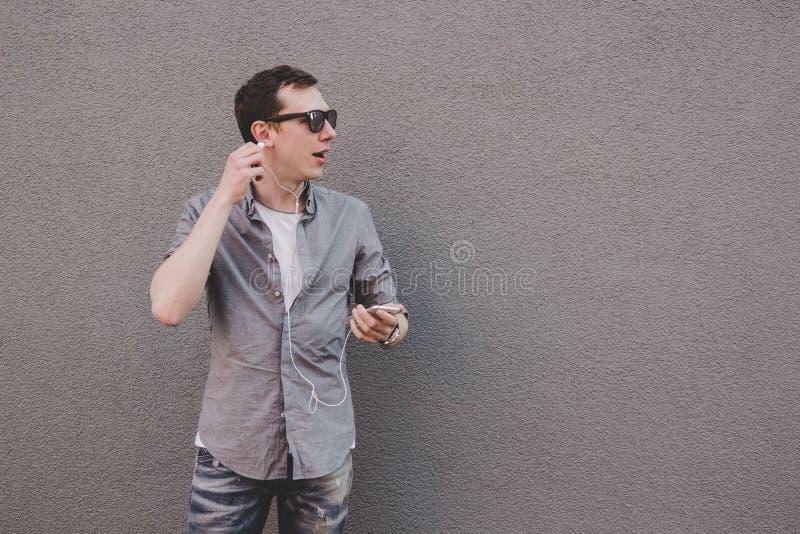 Hombre de risa joven del inconformista que usa su smartphone, música que escucha y mirando la cámara con la atención foto de archivo