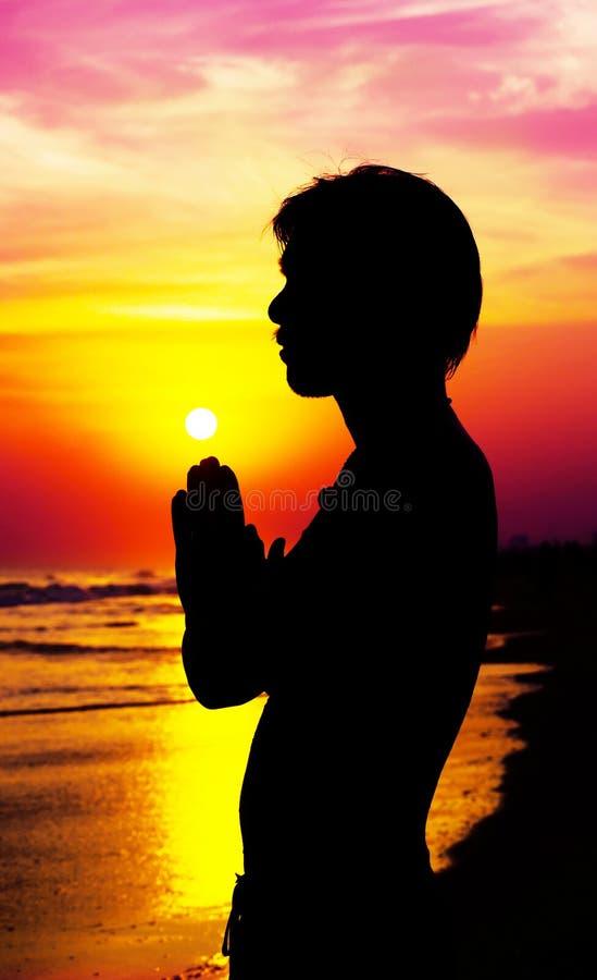 Hombre de rogación en puesta del sol foto de archivo libre de regalías