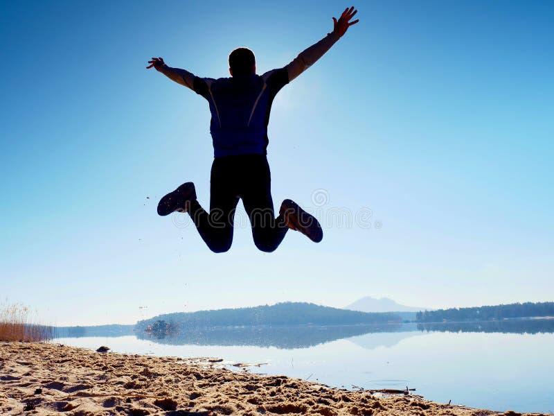 Hombre de salto Salto loco del deportista y el activar en la playa durante la salida del sol fotografía de archivo
