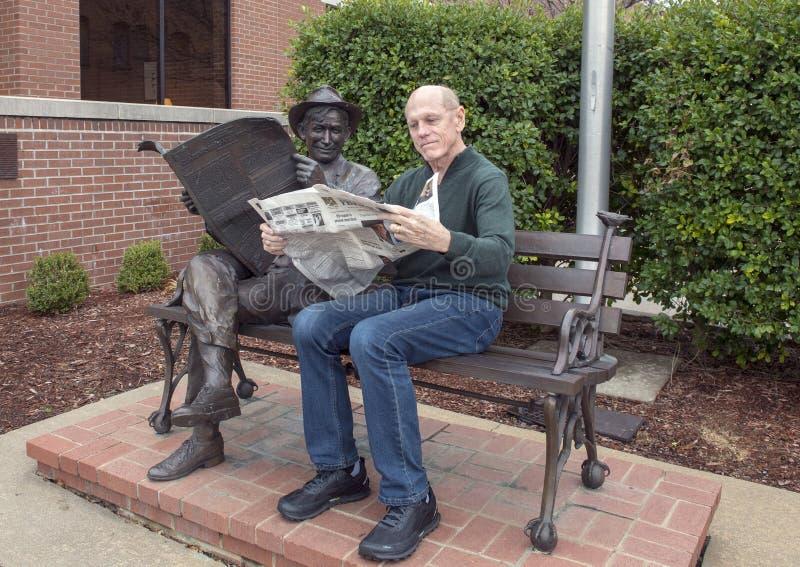 Hombre de setenta años que presenta chistoso con el bronce de la voluntad Rogers en un banco, Claremore, Oklahoma foto de archivo libre de regalías