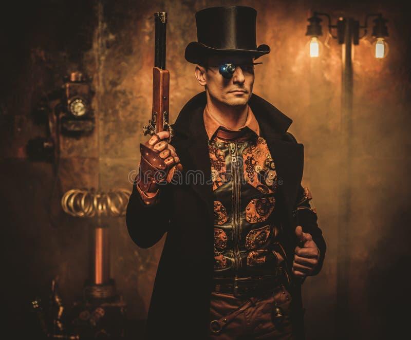 Hombre de Steampunk con el arma en fondo del steampunk del vintage fotos de archivo