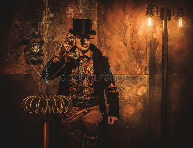 Hombre de Steampunk con la bobina de Tesla en fondo del steampunk del vintage fotografía de archivo libre de regalías