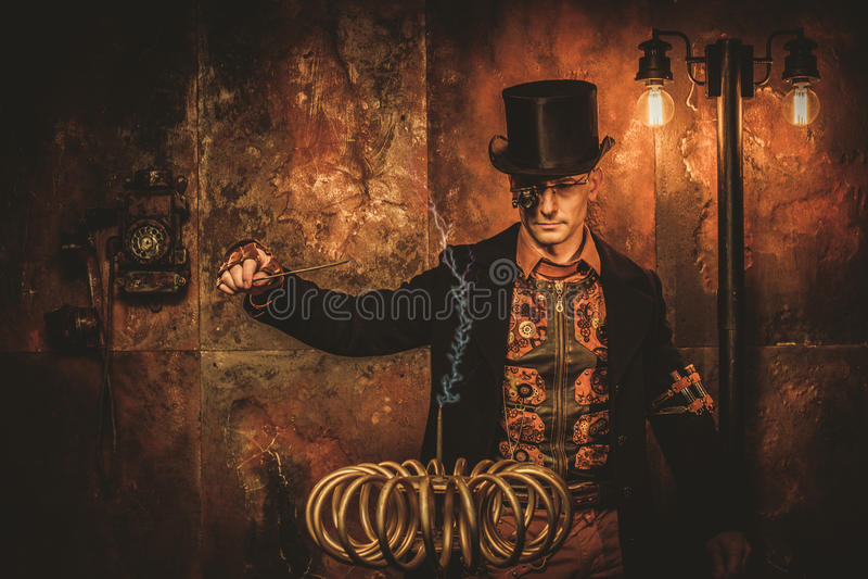 Hombre de Steampunk con la bobina de Tesla en fondo del steampunk del vintage fotografía de archivo