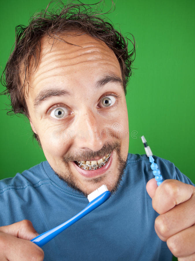 Hombre de treinta años con apoyos y un cepillo de dientes imágenes de archivo libres de regalías