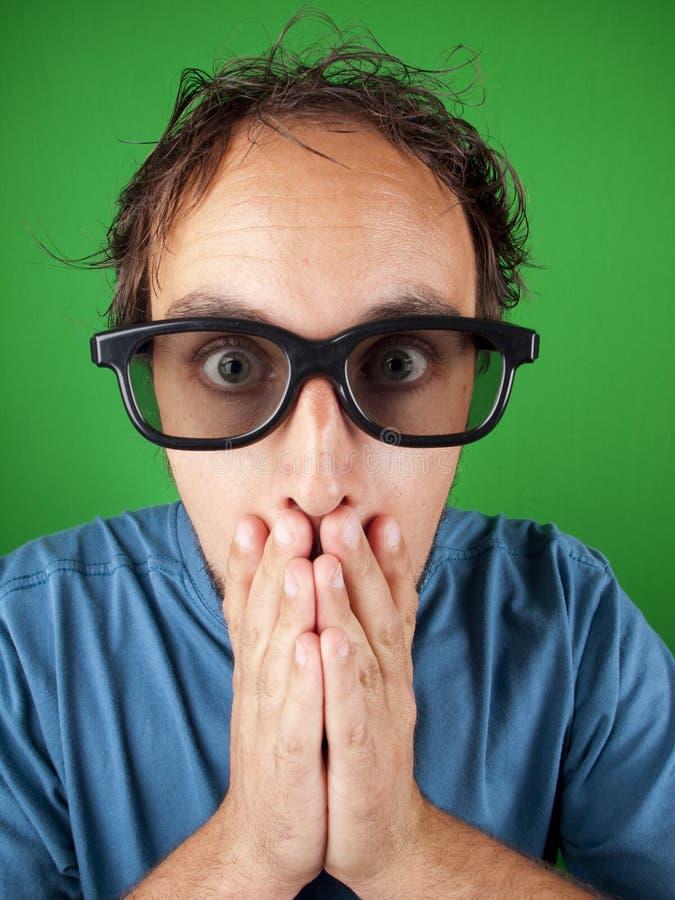 Hombre de treinta años con los vidrios 3d en choque que mira una película imagen de archivo libre de regalías