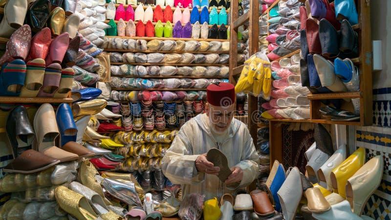 Hombre de Unkown que vende los deslizadores y los zapatos en tienda tradicional en Fes, Marruecos imagenes de archivo