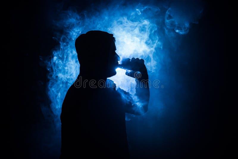Hombre de Vaping que lleva a cabo una MOD Una nube del vapor Fondo negro Vaping un cigarrillo electrónico con mucho humo Concepto foto de archivo libre de regalías