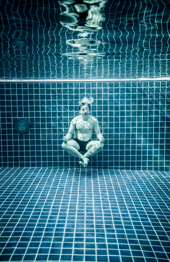 Hombre debajo del agua en una piscina a relajarse en el positio del loto imágenes de archivo libres de regalías