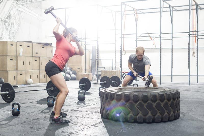 Hombre dedicado y mujer que golpean el neumático con la almádena en gimnasio del crossfit imagen de archivo libre de regalías
