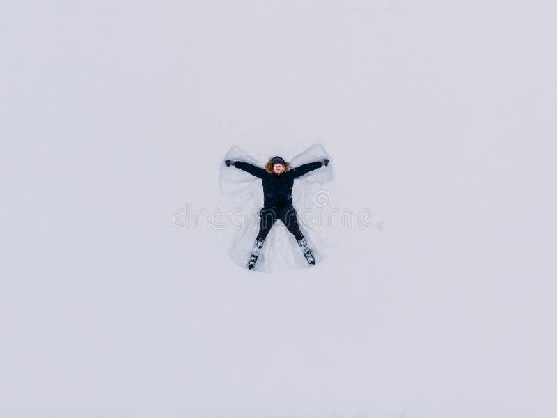 Hombre del ángel de la nieve de la visión superior en diciembre foto de archivo