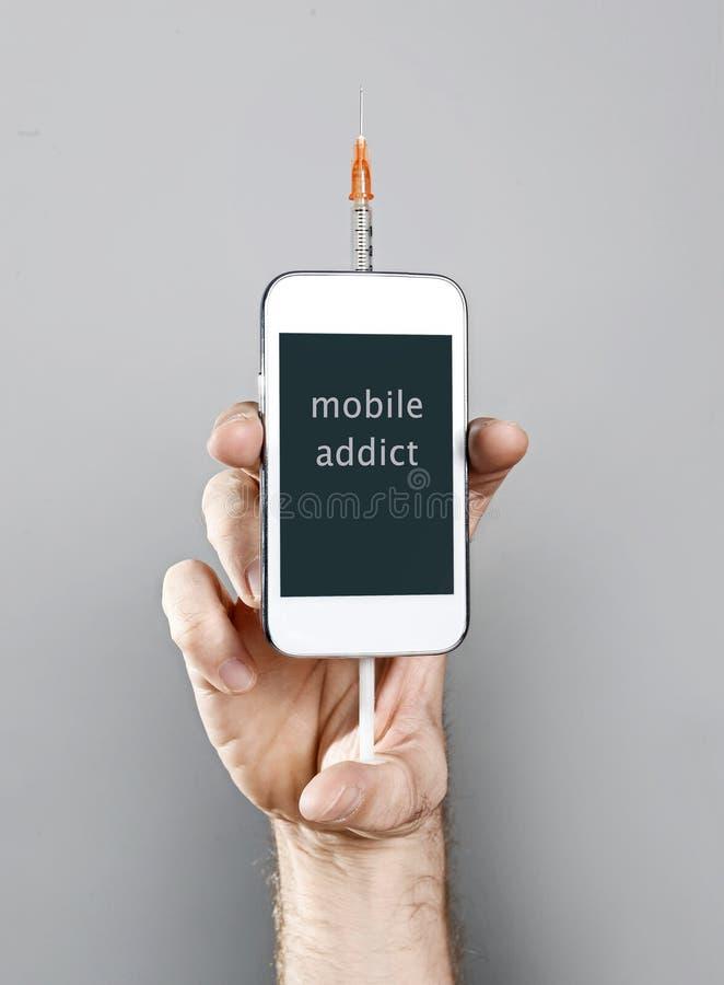 Hombre del adicto al teléfono móvil de Internet que sostiene el teléfono móvil con la jeringuilla en concepto del apego imagenes de archivo