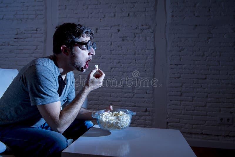 Hombre del adicto a la televisión en el sofá que ve la TV y que come las palomitas en vidrios divertidos del friki del empollón foto de archivo libre de regalías